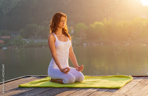 Fotografia  Woman Yoga - relax on the pier at the lake