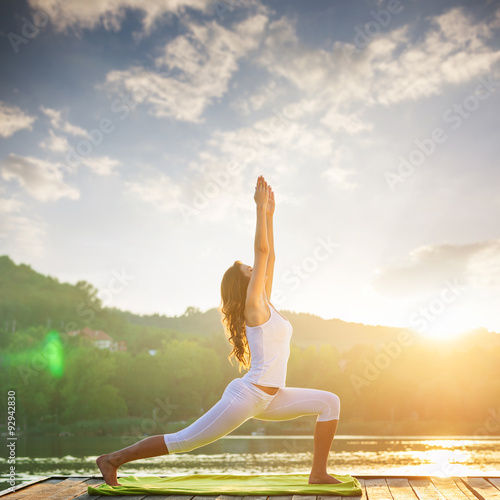 Stampa su Tela  Woman doing yoga on the lake - beautiful lights