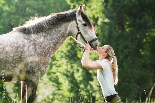 Fotografie, Obraz  Mladá žena küsst ihr Pferd