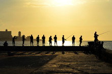 Every Day, Before Sunset, Dozens Of Fishermen Meet In The Malecon (Havana's Harbour, Cuba). Here You Can Observe Some Of Them With Their Shadows, And The Beautiful Sunset In The Background.