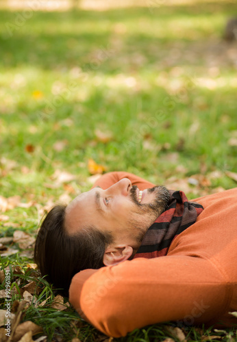 Fotografia, Obraz  Handsome middle-aged man lying on the autumn leaves in park