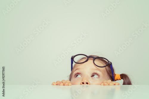 cute little girl hiding behind the table