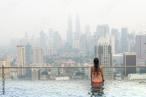 Photo Stands Kuala Lumpur Beautiful woman in swimming pool watching the city