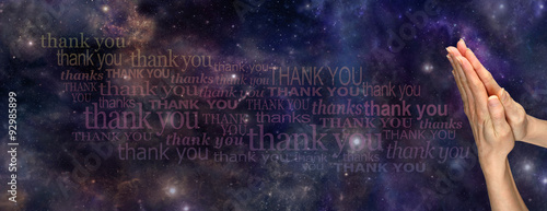 A Prayer of Thanks to the Universe     - Female hands in prayer position on a deep space background with the words 'Thank You' streaming across the page