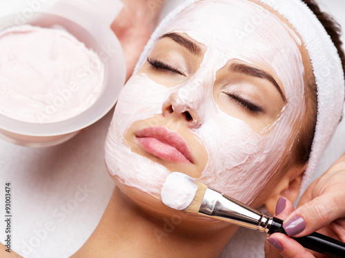 Young beautiful woman receiving facial mask in spa beauty salon