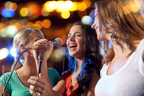 happy young women singing karaoke in night club Wallpaper Mural
