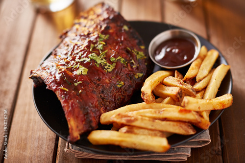 Aluminium Prints Grill / Barbecue half rack barbecue rib platter with french fries on rustic wooden table