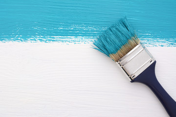 Stripe of turquoise paint with a paintbrush on white
