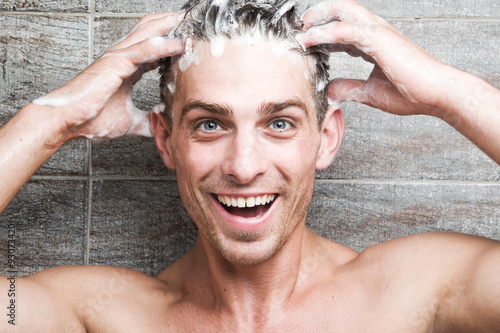 Fotografie, Obraz  Young attractive man cheerfully washes her head