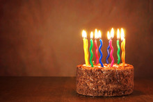 Birthday Chocolate Cake With Burning Candles On Brown Background