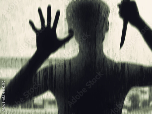 Fotografia  Shadowy figure with a knife behind glass,soft focus