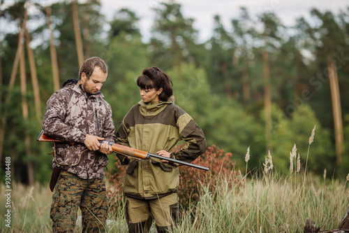 Foto op Aluminium Jacht Instructor with woman hunter aiming rifle at firing nature