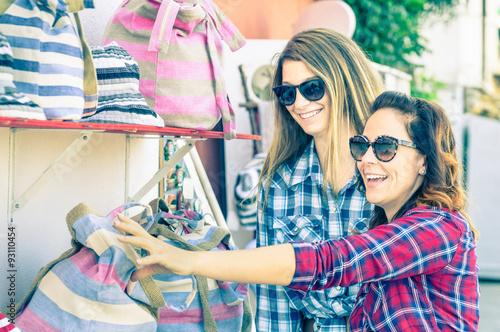 Foto  Young beautiful women girlfriends at flea market looking for bags - Best friends