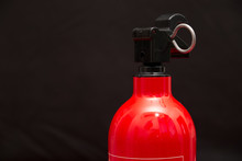 The Top Nozzle Of A Small Fire Extinguisher With A Securing Pin Attached In Front Of A Black Background