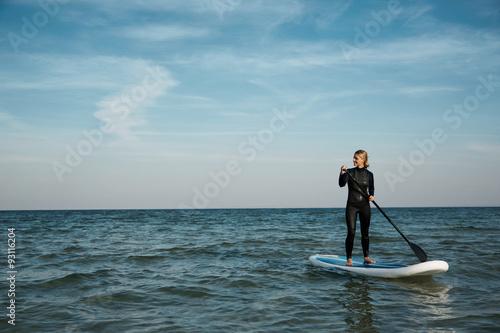 Plakat Młoda blondynki kobieta wiosłuje paddleboard przy morzem.