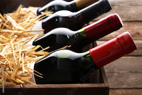 Fotomural Box with straw and wine bottles on wooden background