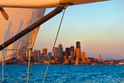 Tuinposter Zeilen Sailing at sunset off Seattle, with the city skyline in the background, sail in the foreground. Copy space