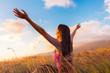 Girl raising arms towards beautiful glowing sunshine.
