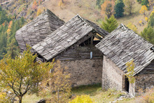 Old Damaged Wooden Roofs Of Abandoned Chalets In Italian Alps