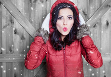 Beautiful  Young Surprised Woman Wearing Winter Hooded Jacket And Gloves Covered With Snow Flakes. Christmas Portrait Concept.