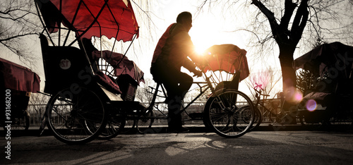 Fotografering  Man Riding a Rickshaw Chinese Occupation Driving Concept