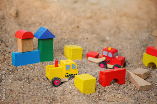 Fotografie, Obraz  toy houses and trucks made of colorful wooden bricks in sandbox