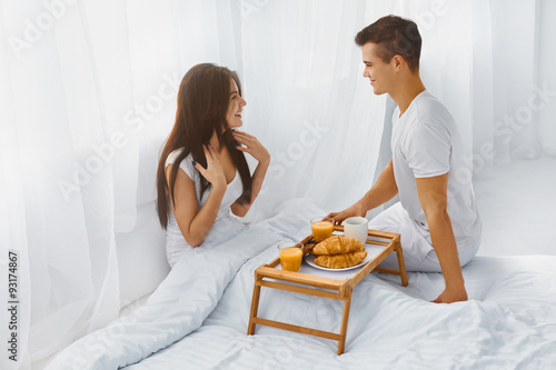 Fotografering  Man surprising woman with breakfast in bed