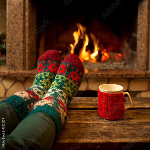 Deurstickers Ontspanning Feet in woollen socks by the Christmas fireplace. Woman relaxes by warm fire with a cup of hot drink and warming up her feet in woollen socks. Close up on feet. Winter and Christmas holidays concept.