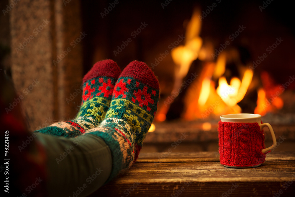 Fototapety, obrazy: Feet in woollen socks by the Christmas fireplace. Woman relaxes by warm fire with a cup of hot drink and warming up her feet in woollen socks. Close up on feet. Winter and Christmas holidays concept.