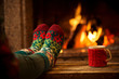 Leinwandbild Motiv Feet in woollen socks by the Christmas fireplace. Woman relaxes by warm fire with a cup of hot drink and warming up her feet in woollen socks. Close up on feet. Winter and Christmas holidays concept.