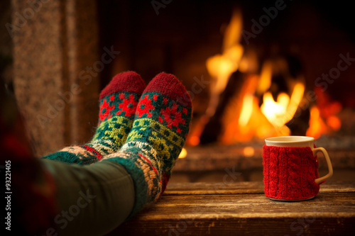 Garden Poster Relaxation Feet in woollen socks by the Christmas fireplace. Woman relaxes by warm fire with a cup of hot drink and warming up her feet in woollen socks. Close up on feet. Winter and Christmas holidays concept.