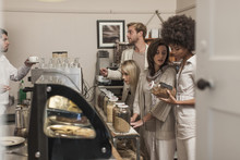 Customers Queuing At Cake Counter In Coffee Shop