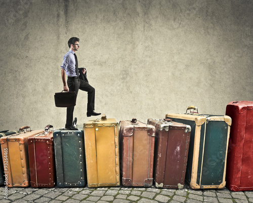 Papiers peints Retro Businessman climbing on a staircase made of suitcases