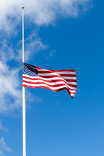 American Flag Flying At Half Mast Against Blue Sky With White Clouds. Copy Space