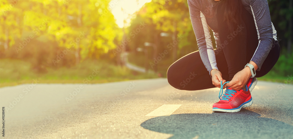 Fototapety, obrazy: Female runner tying her shoes preparing for a jog