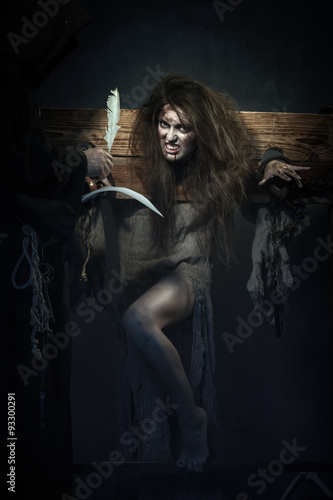 Fotografie, Obraz  Halloween. The Middle Ages. Witch sign a verdict of the Inquisit