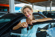 Happy woman standing near a car with keys in hand - concept of b