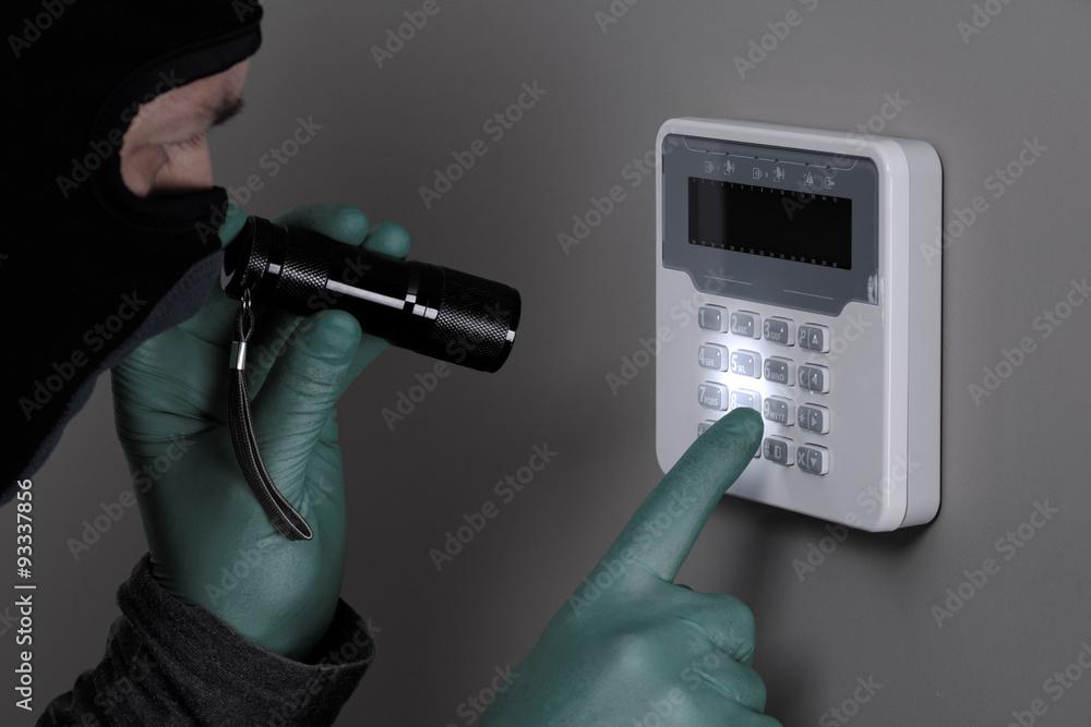 Fototapeta Włamywacz rozbraja system alarmowy