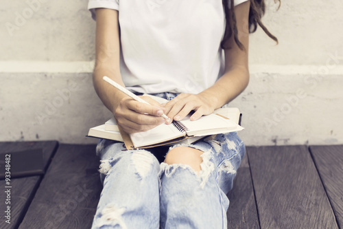 Obraz Girl making notes in the diary and sitting on a wooden floor - fototapety do salonu