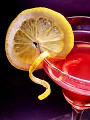 FototapetaPart of pomegranate drink with lemon on black background.