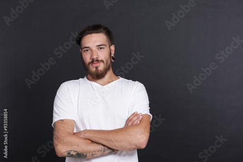 Foto  Junger bärtiger Mann mit Tattoos vor schwarzer Wand und verschränkten Armen