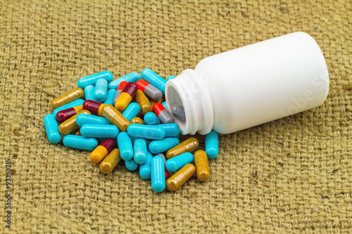 colorful pills and white bottle tablets on brown sack fabric