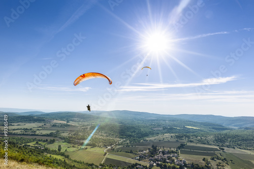Spoed Fotobehang Luchtsport Two paragliders under the rays of a white sun