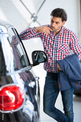 Fotografía  Interested man  examines a new car in showroom