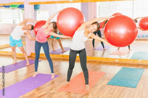 Zdjęcie XXL Piękne wielorasowe kobiety i człowiek robi ćwiczenia z gimnastyczne piłkę.