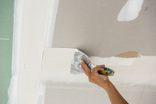 Man Hand With Trowel Plastering A Ceiling, Skim Coating Plaster