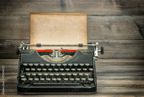In de dag Retro Antique typewriter with grungy worn paper page on wooden table