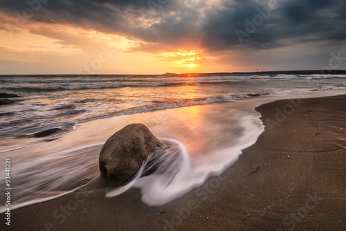 Tuinposter Chocoladebruin Sea sunrise. Amazing sea sunrise with slow shutter and waves flowing out.