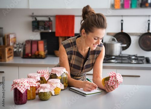 Photo  Woman in kitchen listing ingredients in vegetable preserves
