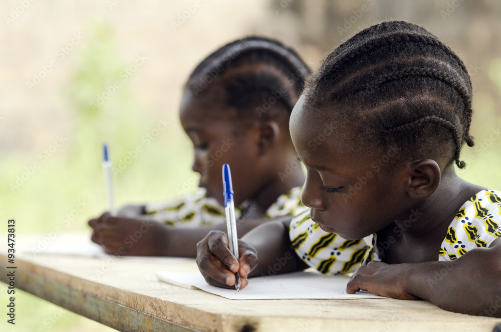 Fototapety, obrazy: African Children at School Doing Homework. African ethnicity students writing their essay in an African school. They're holding blue pens to write down their homework whilst sitting in their desk.